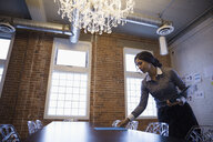 Businesswoman preparing for meeting placing paperwork on table in conference room - HEROF30484