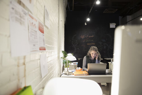 Creative businesswoman working late at laptop in open plan office - HEROF30490