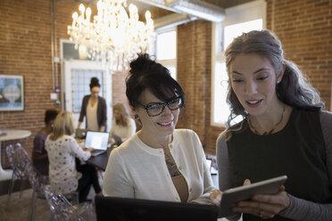 Businesswomen using digital tablet in conference room - HEROF30499