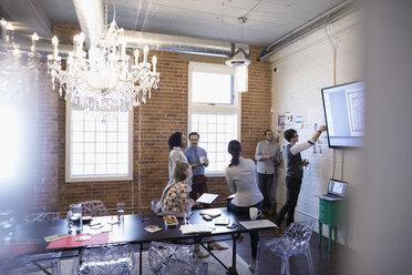 Designers meeting brainstorming reviewing proofs in conference room - HEROF30523