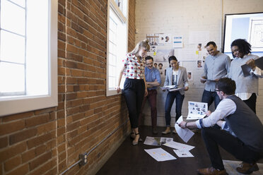 Designers meeting and brainstorming reviewing proofs in conference room - HEROF30526