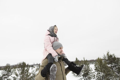 Father carrying little daughter on his shoulders in winter - EYAF00030