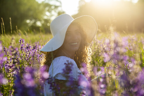 Portrait of smiling woman with summer hat on flower meadow at evening twilight - SARF04173