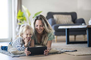 Smiling mother and son lying on the floor at home using tablet - SBOF01911