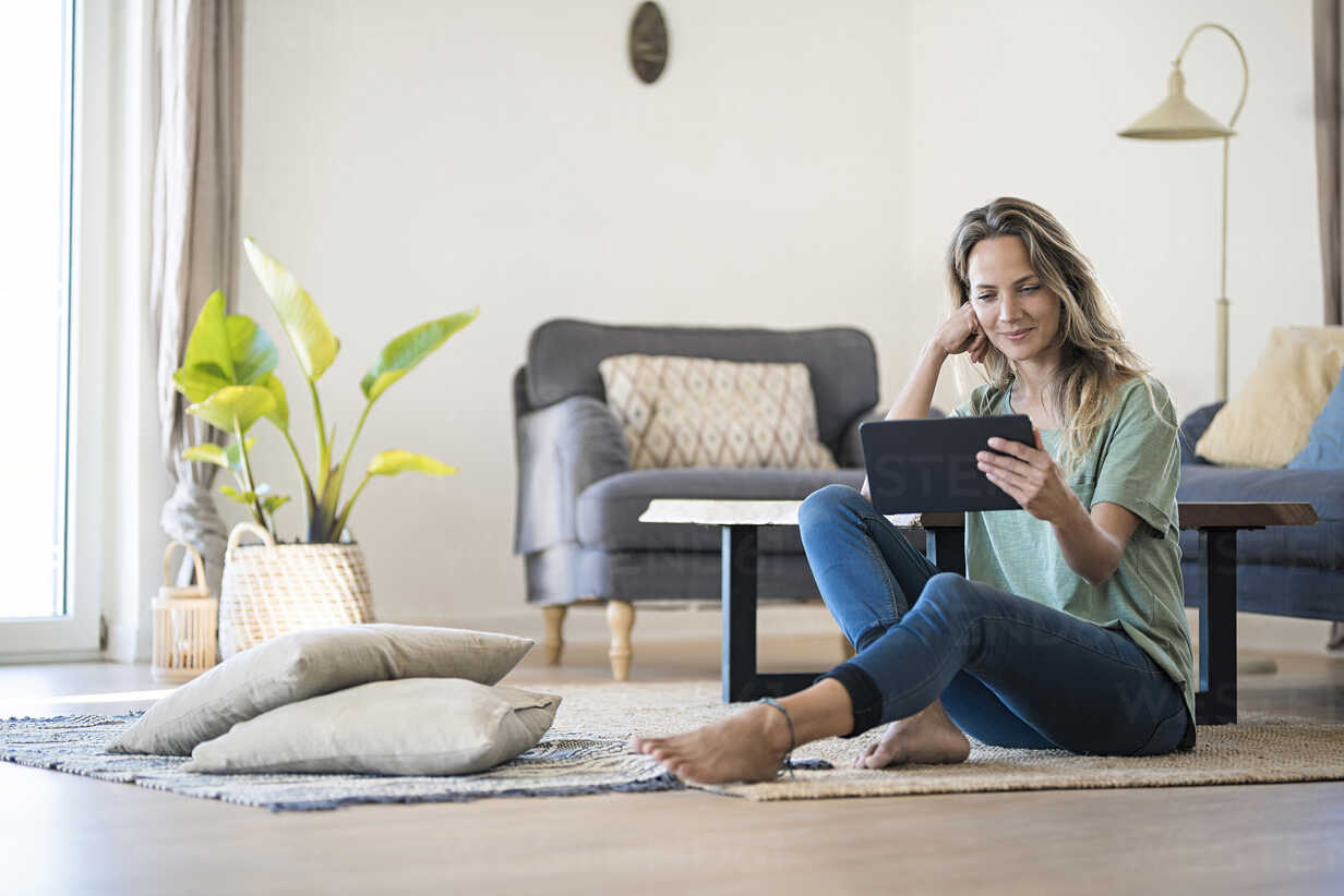 Smiling woman sitting on the floor at home using tablet - SBOF01914 - Steve Brookland/Westend61