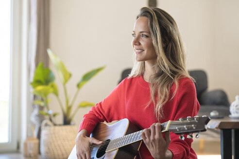smiling blonde woman sitting on floor in modern living room  playing guitar - SBOF01923