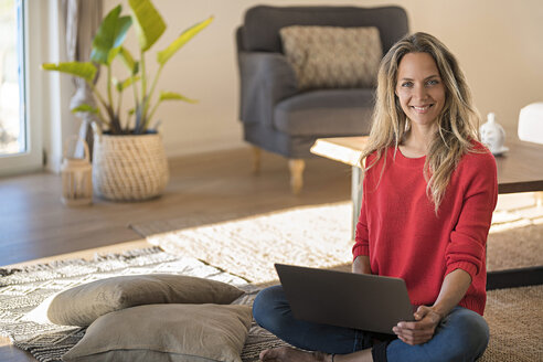 Portrait of smiling woman sitting on the floor at home using laptop - SBOF01929