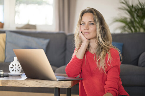 Pensive woman with laptop on coffee table at home - SBOF01932