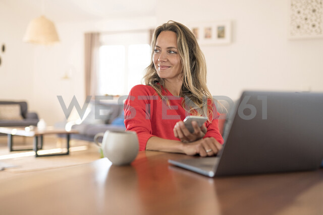 Smiling woman using laptop and cell phone on dining table at home - SBOF01935 - Steve Brookland/Westend61