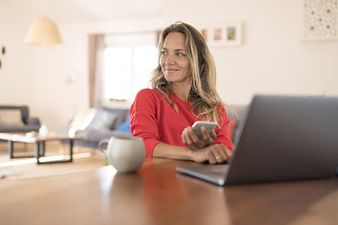 smiling blonde woman sitting at her kitchen table in modern living room having a break from her work at the laptop and holding her smartphone in her hand - SBOF01935