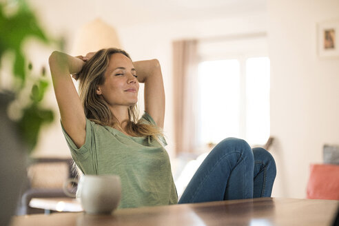 smiling blonde woman sitting at her kitchen table taking a break and leaning back with closed eyes - SBOF01944