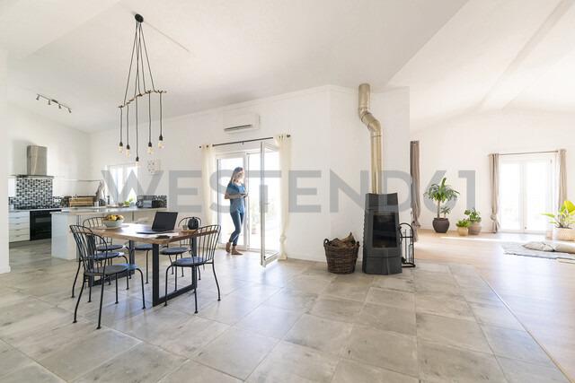 Woman standing in door frame of modern living room with fireplace - SBOF01953 - Steve Brookland/Westend61