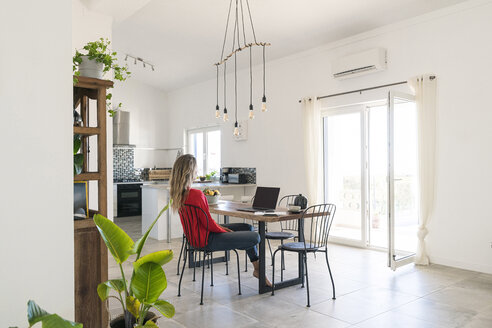 Woman using laptop on dining table in modern home - SBOF01956