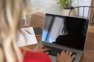 Close-up of woman using laptop on wooden table at home - SBOF01959
