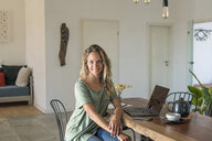 Portrait of smiling woman with laptop sitting at dining table at home - SBOF01962
