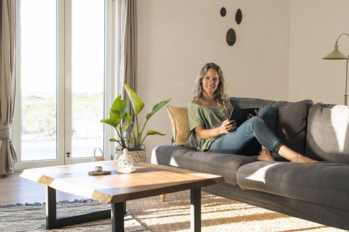 smiling blonde woman relaxing on couch holding tablet in modern contemporary living room - SBOF01965