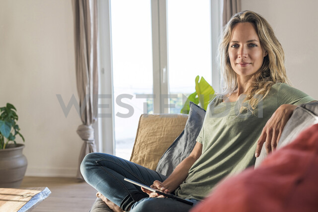 Portrait of smiling woman realxing on couch at home with tablet - SBOF01968 - Steve Brookland/Westend61