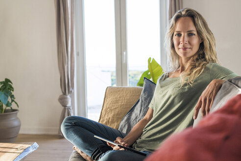 smiling blonde woman relaxing on couch holding tablet in modern contemporary living room - SBOF01968