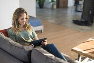 Woman realxing on couch at home using tablet - SBOF01971