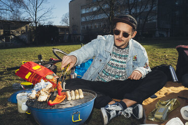 Young man having a barbecue in park - GCF00246