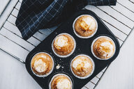 Home-baked muffins in muffin tray on cooling grid - ERRF00805