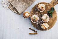 Home-baked muffins with cinnamon and mint on wooden board - ERRF00811