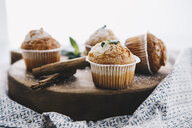 Home-baked muffins with cinnamon and mint on wooden board - ERRF00814