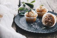 Home-baked muffins with cinnamon and mint on plate - ERRF00817