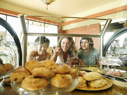 Three young women staring at pastries on display in cafe, one woman pointing, view through glass - JUIF00061