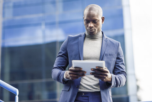Portrait of smart businessman using digital tablet outdoors - JSMF00886