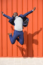 Successfull businessman jumping in the air in front of orange wall - JSMF00898