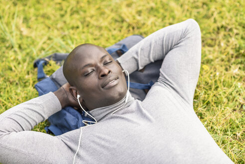 Portrait of businessman lying on a meadow listening music with earphones - JSMF00910