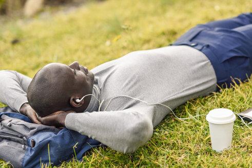 Businessman lying on a meadow listening music with earphones - JSMF00913