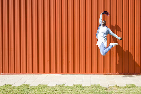 Man wearing casual denim clothes jumping in the air in front of orange wall - JSMF00925