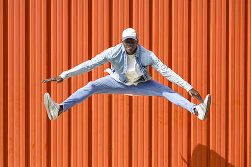 Man wearing casual denim clothes jumping in the air in front of orange wall - JSMF00928