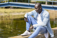 Man wearing casual denim clothes sitting near river using smartphone - JSMF00937