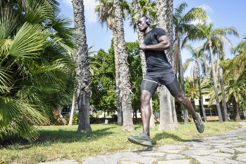 Spain, Andalusia, Malaga. Black man with athletic body running outdoors in sportswear. Fitness concept. - JSMF00952