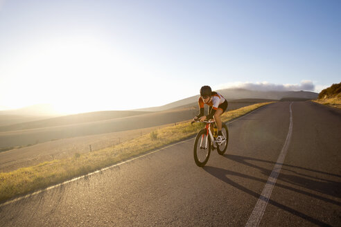 Female cyclist riding race bicycle on sunny open road - JUIF00197