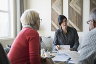 Financial advisor explaining paperwork meeting with senior couple in living room - HEROF30600