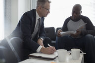 Financial advisor discussing paperwork with man in living room - HEROF30609