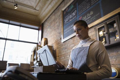 Female spice shop owner using digital tablet cash register at shop counter - HEROF30618