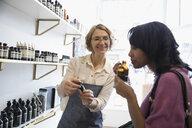 Female shop owner helping woman smelling home fragrances in shop - HEROF30630