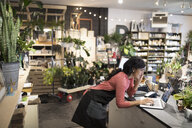 Female shop owner talking on cell phone working at laptop at plant shop counter - HEROF30651