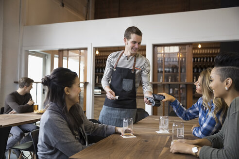 Female friends paying waiter with smart phone contactless payment in brewery tasting room restaurant - HEROF30660