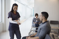 Female nurse with medical chart talking to male patient in waiting room - HEROF30717
