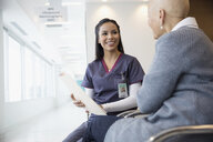 Female nurse discussing medical chart with bald cancer patient in waiting room - HEROF30720