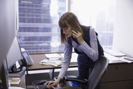 Female lawyer talking on cell phone and working at computer in office - HEROF30789