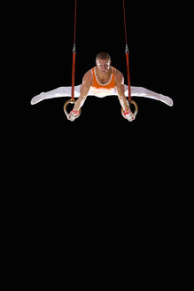 Male gymnast performing on gymnastic rings, portrait, low angle view - JUIF00217