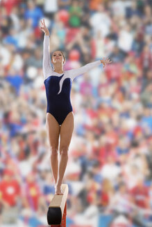 Female gymnast performing on balance beam, portrait, low angle view - JUIF00220