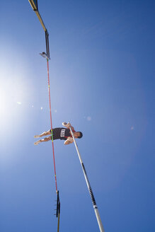 Pole vault athlete going over bar, low angle view (lens flare) - JUIF00232